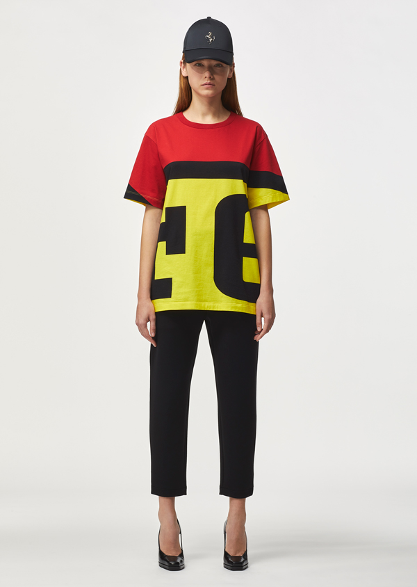 Full-length picture of a woman wearing a yellow, red and black oversize t-shirt with Ferrari maxi logo